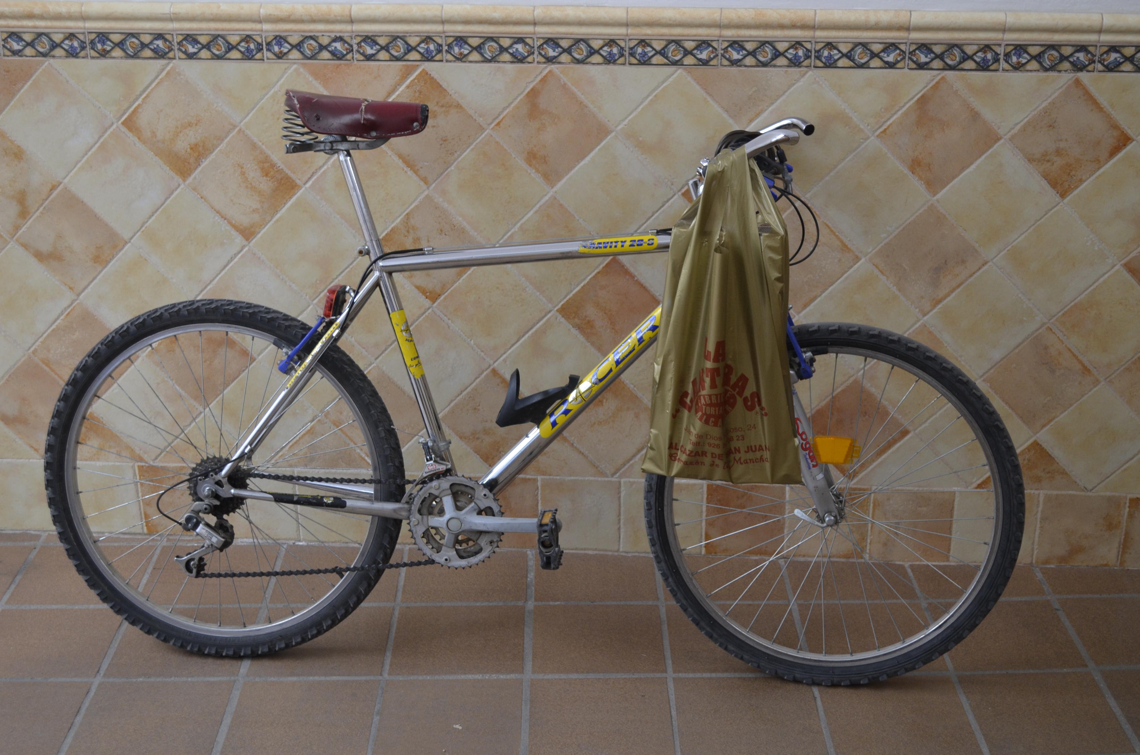 Bolsa con docena de tortas de Alcazar enganchada en el manillar de la bicicleta par recoger los pedidos en el horno y llevarlo a la empresa de transportes
